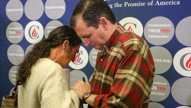 Sen. Ted Cruz, R-Texas, shares a moment to pray with Kristi Berg at the Crossroads Shooting Sports gun shop on Dec. 4, 2015, in Johnston, Iowa.