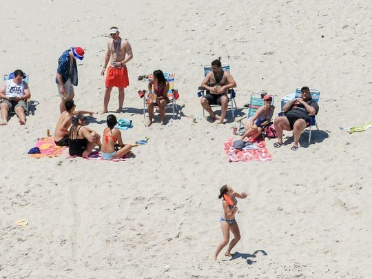 Gov. Chris Christie, right, uses the beach with his family and friends at the governor's summer house at Island Beach State Park on July 2, when the park was otherwise closed to the public due to the government shutdown. The after-effects of Christie's ill-advised trip are still being felt.