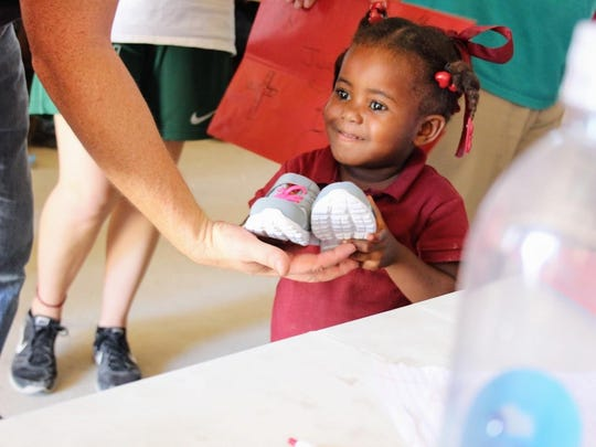 A Haitian girl is given a pair of shoes by Mitch Varnes