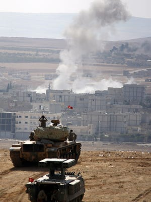 Turkish soldiers on tanks watch the fighting in Kobani, Syria, on Thursday.