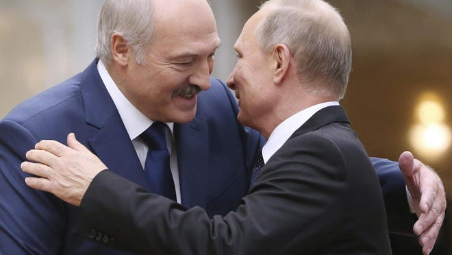 FILE- In this file photo taken on Thursday, Nov. 30, 2017, Belarusian President Alexander Lukashenko, left, greets Russian President Vladimir Putin during the Collective Security Council of the Collective Security Treaty Organization (CSTO) summit in Minsk, Belarus. Putin warned that he stands ready to send police to Belarus if protests there turn violent, but added in an interview broadcast Thursday that there is no such need now and voiced hope for stabilizing the situation in the neighboring country.
