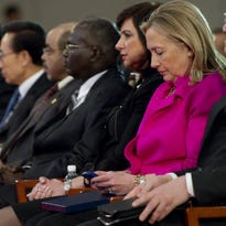 In this Nov. 30, 2011 file photo, Secretary of State Hillary Clinton checks her phone in Busan, Korea.