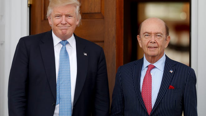 President-elect Donald Trump pauses for photographs with investor Wilbur Ross as he leaves the Trump National Golf Club Bedminster clubhouse, Sunday, Nov. 20, 2016, in Bedminster, N.J..