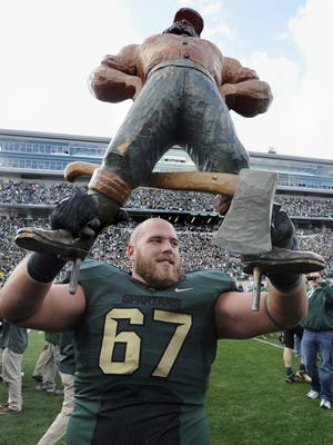 LSJ file MSU offensive guard Joel Foreman holds up the Paul Bunyan Trophy to celebrate the Spartans' fourth straight win over Michigan, a 28-14 victory on Oct. 15, 2011.