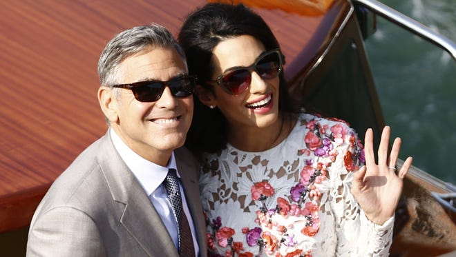 George Clooney and his wife Amal Alamuddin stand on a taxi boat on the Grand Canal on September 28, 2014, in Venice.