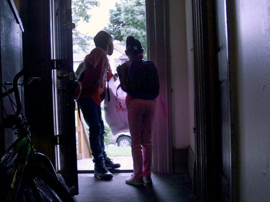 Samir Waddell, left, takes the garbage out for his mother as he and his sister Sanijah Waddell head out from their Grieg Street home for school.