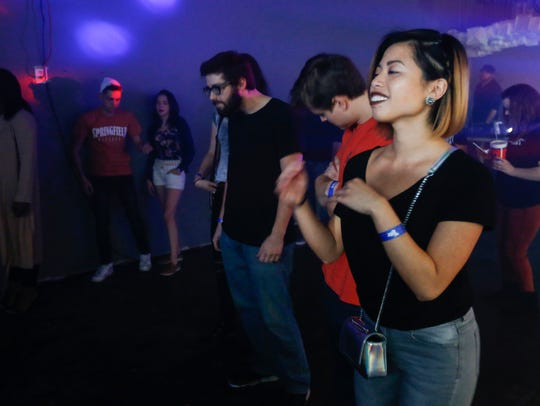 Concert goers dance during a performance at The Drop