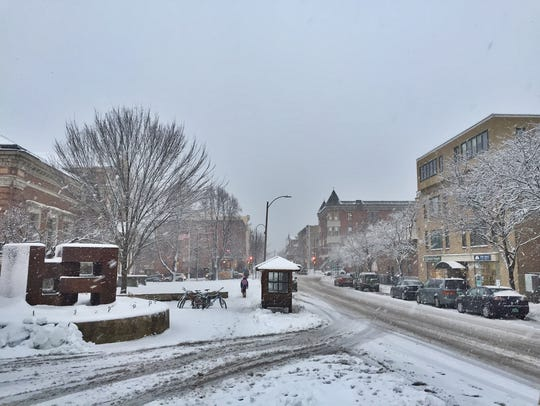 Snow falls along College Street in Burlington late