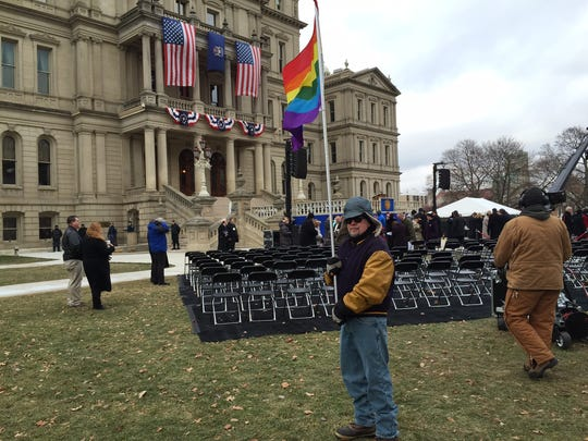 Bob Fluke of Lansing holds a gay pride flag at Gov. Snyder's inauguration.