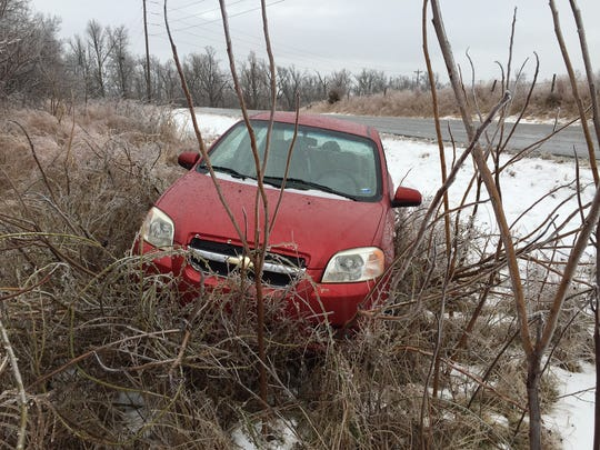 A car sits stranded after sliding off icy Hand Cove Road on Saturday morning.