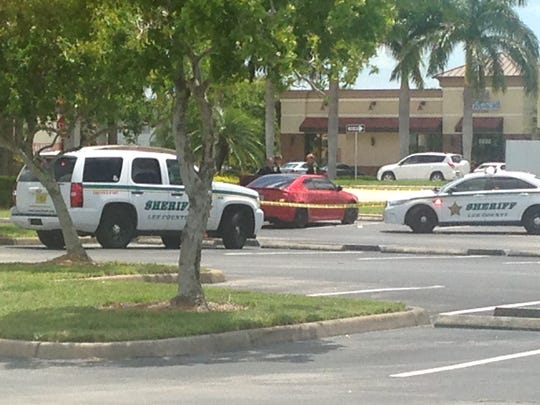 Police tape surrounds a red coupe in the parking lot near Eyeglass World at Page Field Commons in Fort Myers. Deputies are investigating a stabbing.