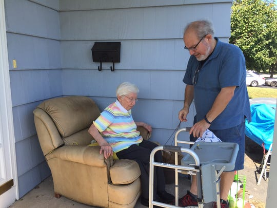 Robert St. George, right, helps his mother, Rose St. George, 93, into her porch chair that the Town of Irondequoit says is a code violation.