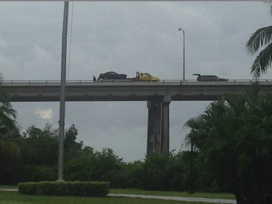 The car a man crashed into the side of the Caloosahatchee Bridge before he jumped into the river to avoid police is hauled away Tuesday.