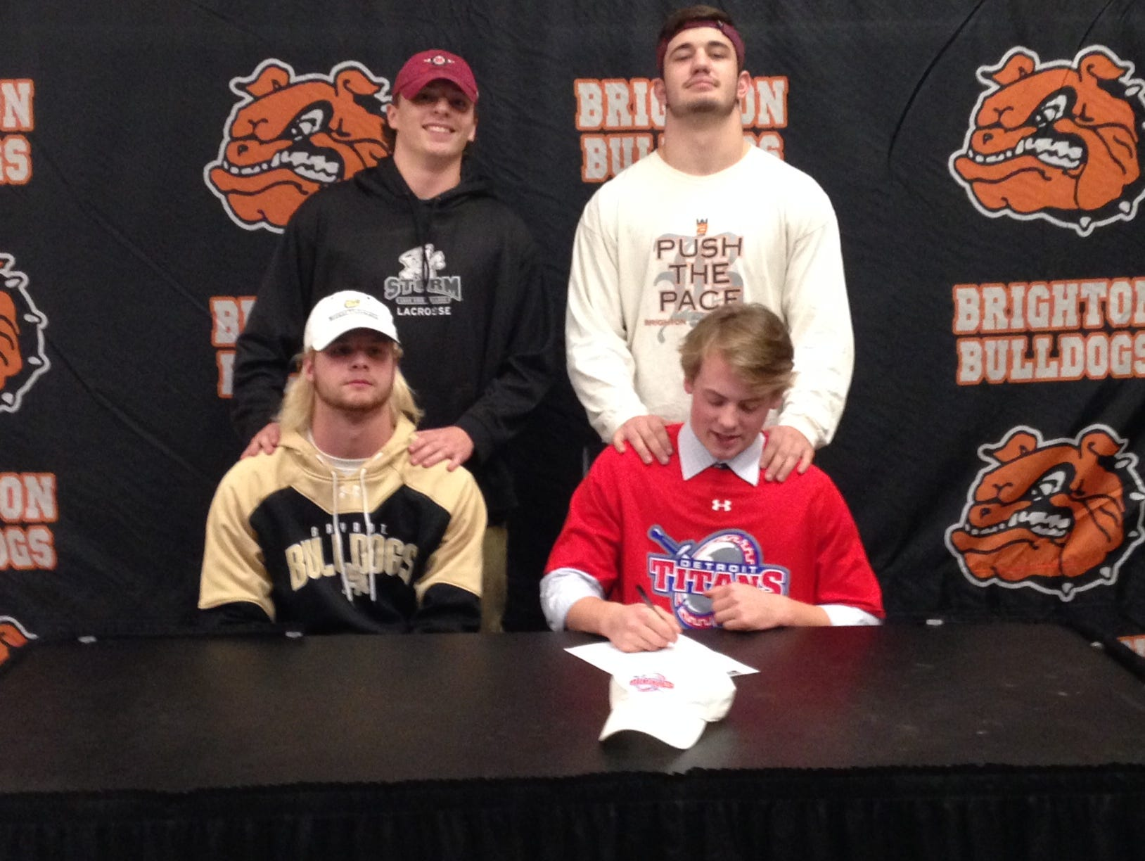 Brighton's Dylan Mercier, lower right, signs his letter of intent to play at University of Detroit next season alongside teammates Jack Aigner, lower left, Luke Ready, top right, and Jake Derosiers, top left.