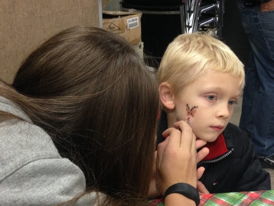 Jordan Smith, 8, of Farmington, gets his face painted at the Stuff the Bus event in Victor Saturday,