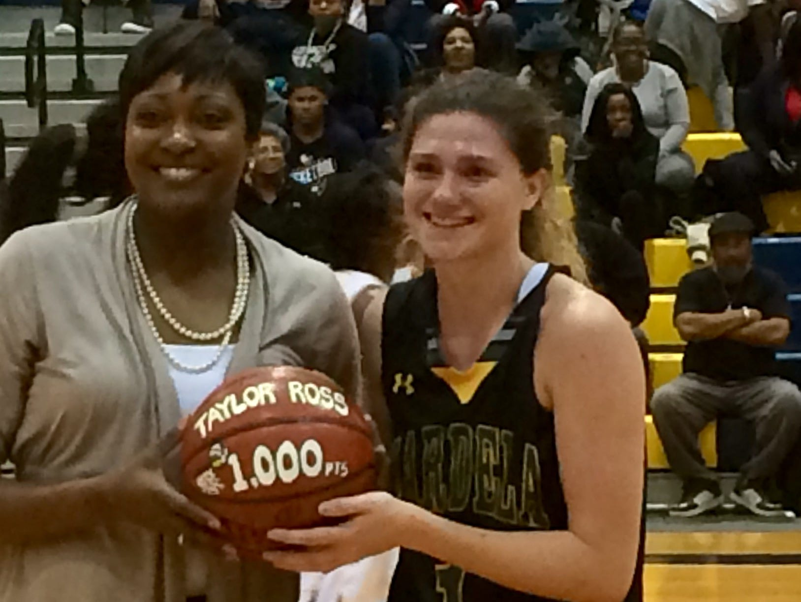 Mardela head coach Kesha Cook presents Taylor Ross with a commemorative ball after she scored her 1,000th point.