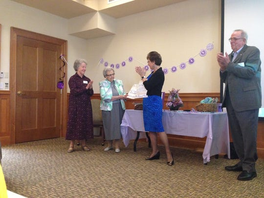 Miriam Mills presents a check for $3000 to Heifer International at her 90th birthday celebration.