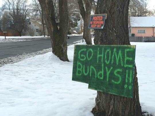 A sign tacked outside a Burns. Ore., home reflects growing community sentiment that outsider militia aren't welcome, in mid-December 2015. Self-styled patriots and militia say they are in the area to help ranchers Dwight and Steven Hammond, convicted of arson for burning federal land. The sign refers to Ammon Bundy, whose father Cliven Bundy was at the center of an armed standoff in Nevada in 2014.