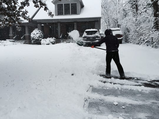 Jennifer Thibadeau shovels snow from the driveway of her West End home on Friday.