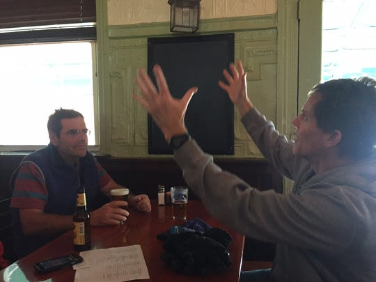 George Hobbs (left) looks on as friend, Mark Manning, explains weather patterns over beers at Kelly's Logan House Saturday. Pubs are a popular option during storms.