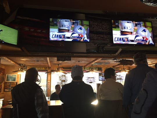 Football fans watch the AFC Championship game on Sunday