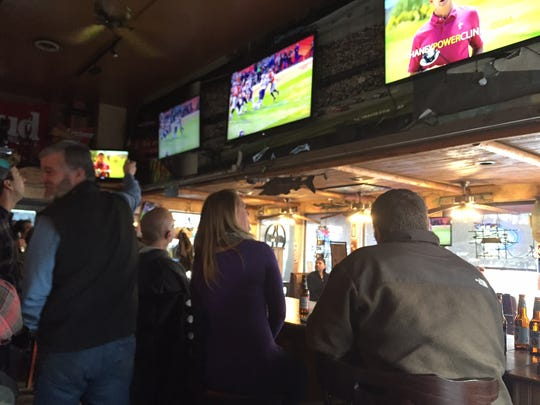 Football fans watch the AFC Championship game on Sunday at The Pour House in South Burlington.