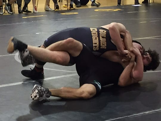Northmor's Ben Singer tries to roll out of the grasp of Clear Fork's John Witischi, who won the 170-pound match by pin.