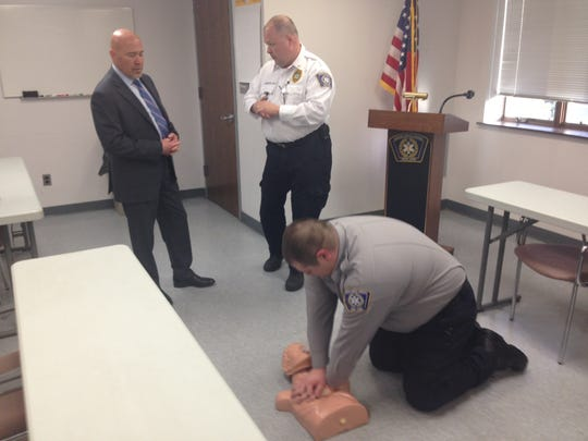 An EMS worker shows Congressman Tom MacArthur how CPR is done. Mount Laurel Emergency Medical Services Chief Joseph Stringfellow (right) talks to MacArthur.