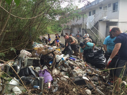 In this file photo, volunteers clean up an illegal dumpsite along the beach access point in Tumon.