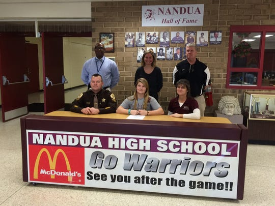 Ryan Wright (center front) signs her letter of intent to play for Salisbury University at Nandua High School. Ryan is joined by her parents, Carl and Dana, along with Nandua principal George Parker, girls soccer assistant coach Lauren Tanis and athletic director Gary Reese.
