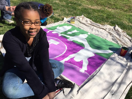 Nine-year-old Sydney Thompson helps paint a panel of the Jefferson Street mural.