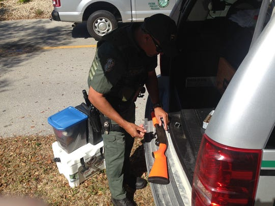 A Florida Fish & Wildlife officer loads noise-maker shells into a shotgun at Three oaks Elementary School on Wednesday. Wildlifem officers were called to the school when a bear was seen walking around and then was cornered up a tree on school grounds.