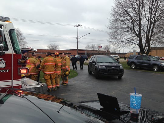 Emmett Township firefighters stand by as Harper Creek High School and middle school are evacuated Monday afternoon. Authorities said they evacuation was a precaution after a note was found at the high school saying a bomb would go off at 2:50 p.m., when school is dismissed.