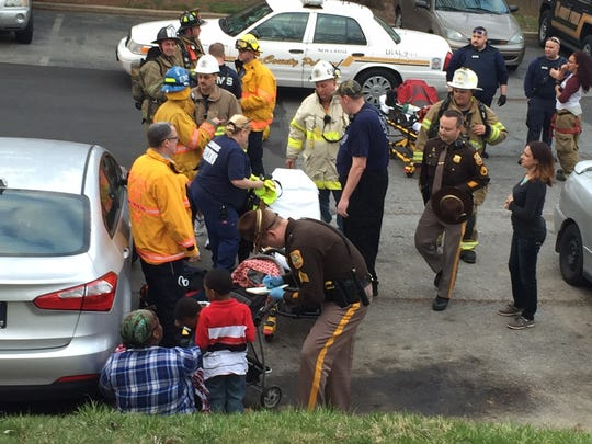 Emergency crews work on people on March 25 at the Riverfront Heights apartments near Wilmington. Officials say a carbon monoxide exhaust pipe on one of the building's boilers was rusted.
