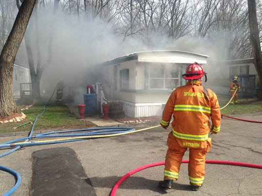 Firefighters battle flames in a trailer at the Avenue A Mobile Home Park in Springfield.