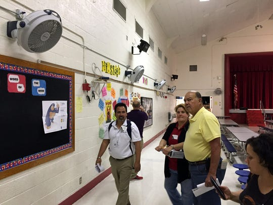 El Paso Independent School District Facilities Advisory Committee members stand under fans mounted to the cafeteria wall at Hillside Elementary School, which doesn't have refrigerated air conditioning.
