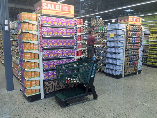 A staff member stocks shelves at the new Whole Foods in Meridian Township, which opens Wednesday.