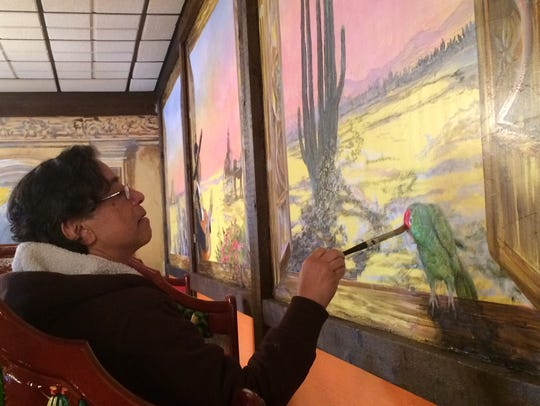 Door County artist Ram Rojas paints his mural at Old