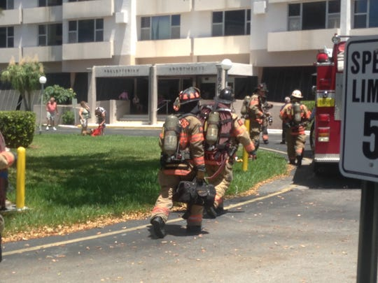 Fort Myers firefighters trudge into the Presbyterian Apartments on Virginia Avenue on Sunday after a resident's cooking produced a lot of black smoke.