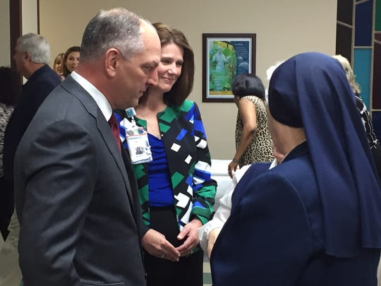 Gov. Edwards and St. Francis President and CEO Kristin Wolkart visit with guests in the hospital's auditorium.