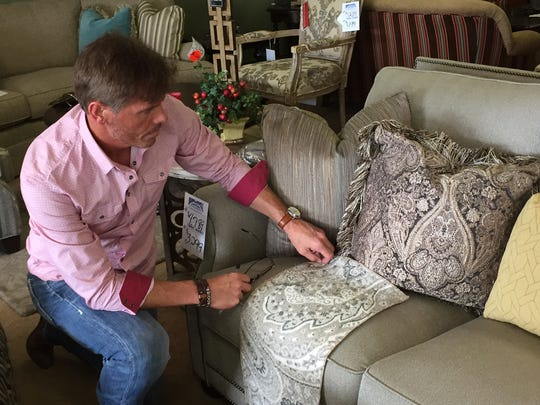 Store manager Tim Glover checks upholstery samples at Burns & Newell Furniture in Monroe.