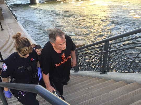 Rescue workers with the Reno Fire Department walk with a man bystanders rescued from the Truckee River on Wednesday evening.