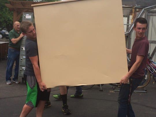 Juniors Keegan Buchkowski, left and Brandon Carlson, right, carry dresser into shelter.