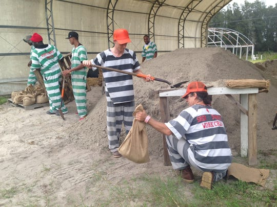 An inmate work crew fills sandbags at the Brevard County Sheriff's Farm as Tropical Storm Colin bears down on Florida.