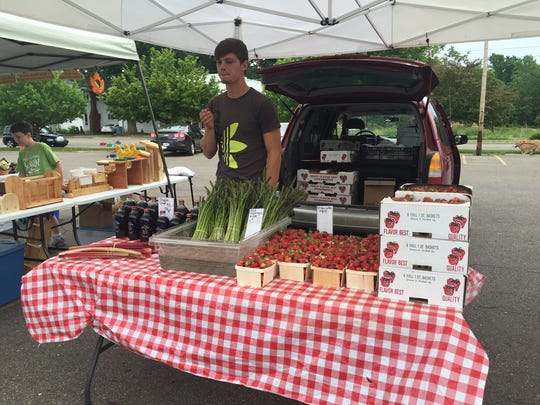 Justin Nightengale of Nightengale Farms talks about the different produce the farm grows at the South Lansing Farmers Market on June 9, 2016.