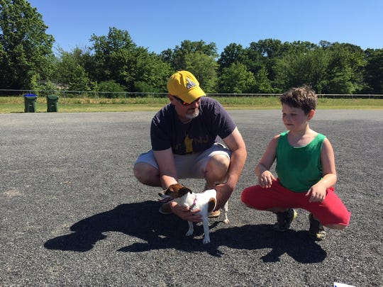 Edison resident Jeff Mullins, his son, Brayden, and their new addition, Emma, spend time Thursday morning at Whitman Avenue Dog Park in Edison.