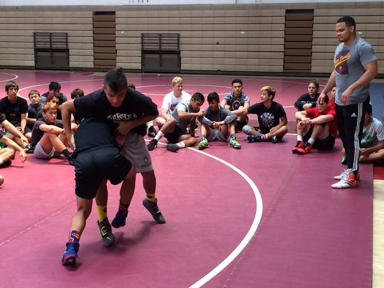 Two-time NCAA champion Chris Pendleton (right) watches campers practice techniques during the La Quinta High School summer wrestling camp on Friday.