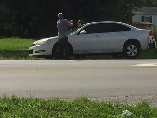 The crime scene at Luckett Road and Ortiz Avenue involved a white Chevy Impala with bullet holes and rear damage in front of the Ortiz Food Store.