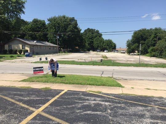 Candidate Bob Sweere puts up political signs along