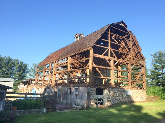 A view of the timber-frame Undersander barn shows disassembly.